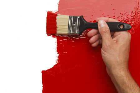hand holding house: Hand Painting Wall Red With White  Copy Space.