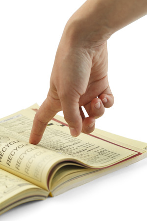 Finger Pointing Searching Yellow Phone Book. Stock Photo