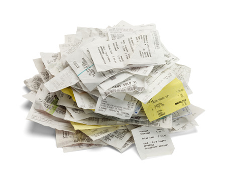 Heap of paper sales receipts in a mound isolated on white background. Imagens