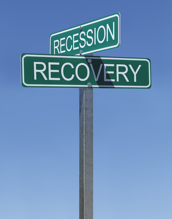 crossroads sign: Two Green Street Signs Recession and Recovery on Metal Pole with Blue Sky Background. Stock Photo