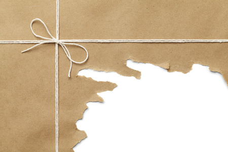 破れている白い背景の上にロープで茶色の紙のパッケージです。 写真素材