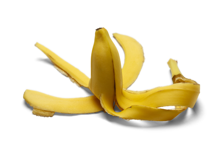 pitfall: Half Eaten Banana with Peel Laying on Ground Isolated on a White Background. Stock Photo