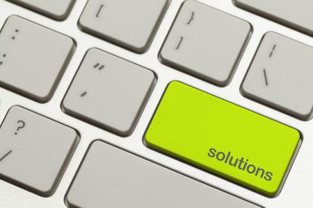 using the computer: Close Up Button Soluciones verde en el teclado. Foto de archivo