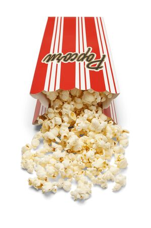 movie popcorn: Box of yellow butter popcorn spilled on the ground isolated on a white background.