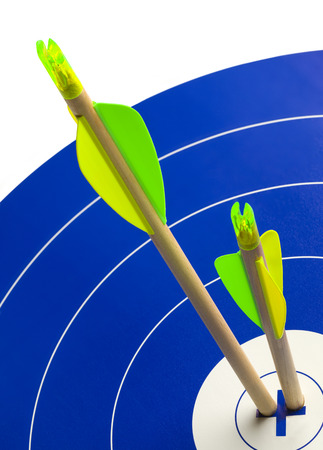 darts flying: Two Wood Arrows in Center of Blue and White Target.
