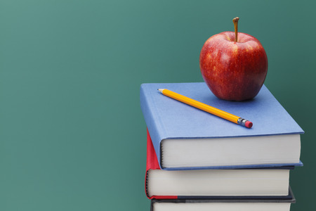 medium close up: Close up of Classroom Chalk Board, Books and Apple with Copy Space. Stock Photo