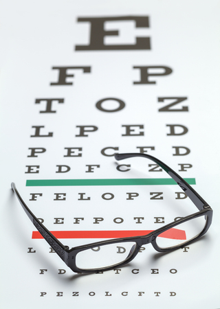 office tool: Pair of Glasses on Eye Exam Chart. Stock Photo