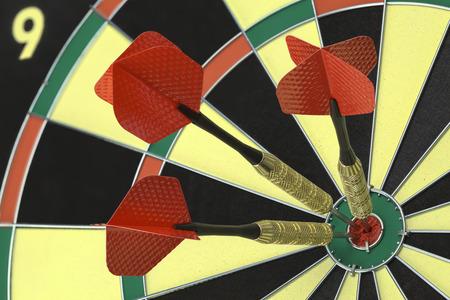 DARTS: Three Darts in the Bulls Eye on Dart Board. Stock Photo