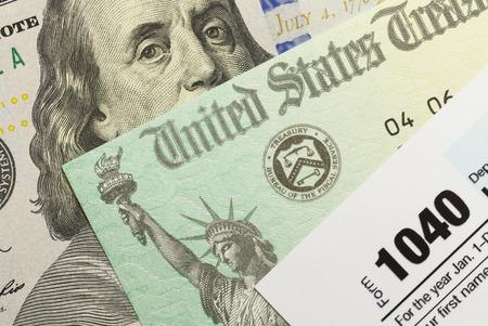 impuestos: 1040 Formulario de impuestos con el cheque de reembolso y el efectivo.