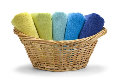 Rieten mand met gevouwen handdoeken die op een witte achtergrond. Stockfoto