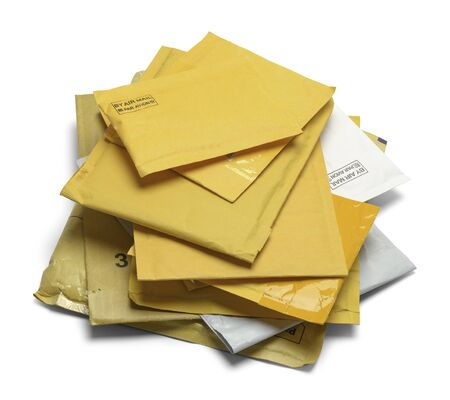 comunicaci�n escrita: Peque�a pila de sobres acolchados amarillo aislado en el fondo blanco.