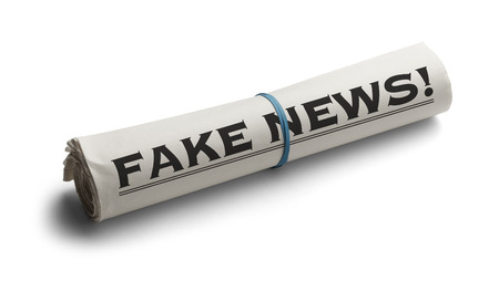 disinformation: Rolled Up Newspaper with Headline of Fake News Isolated on White Background. Stock Photo