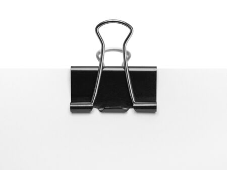 Black Binder Clip on Paper Isolated on White Background.