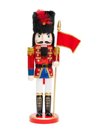 Wood Nut Cracker Doll with Black Hat and Red Flag Isolatedo on a White Background.