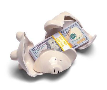 Broken Piggy Bank with Money Inside Isolated on a White Background.