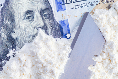 Hundred Dollar Bill With Cocaine Drugs and Razor. Stock Photo