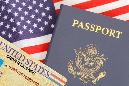 American Passport Close Up With Drivers License on Top of USA Flag.