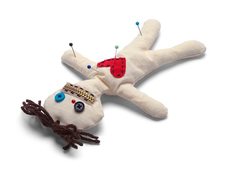 Muñeco vudú con agujas boca abajo aislado sobre fondo blanco. Foto de archivo