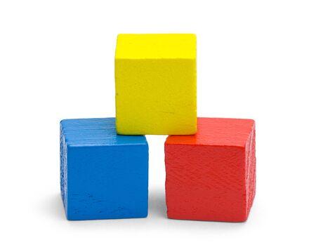 Tre blocchi di legno colorati isolati su sfondo bianco.
