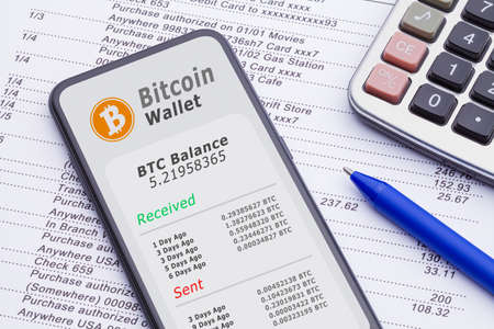 Smart Phone With Bitcoin Wallet on Bank Statement with Calculator and Pen.