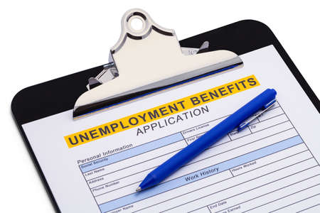 Unemployment Benefits Application on Clipboard with Pen.