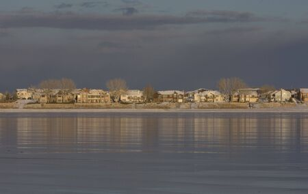 skyline of Colorado houses across frozen lake, winter scenery with reflections in ice Stock Photo - 2283534