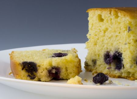 Two slices of cornbread with blueberries on a white plate against dark background Stock Photo - 2289979