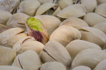 salted pistachios nuts with focus and spot light on a shelled one Reklamní fotografie