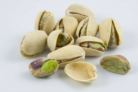 dozen of salted and roasted pistachio nuts on white background, focus on front row Stock Photo - 2302837