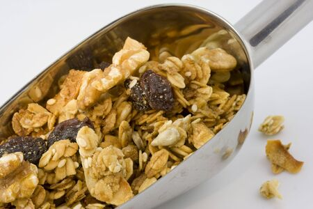 metal scoop full of healthy, organic granola on white background Stock Photo - 2336932