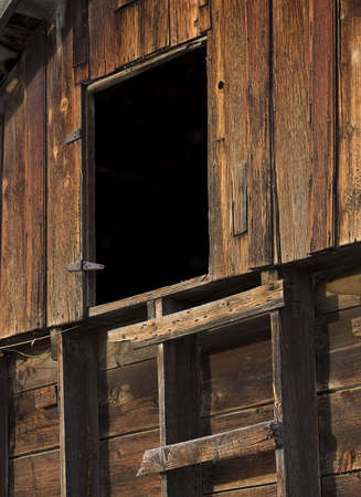 primitive ladder leading to mysterious dark entry - upper level of an old weathered barn photo