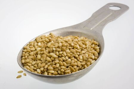 A tablespoon of oil rich sesame seeds on white background Reklamní fotografie