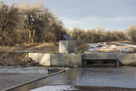 Diversion dam and irrigation ditch on South Platte River in eastern Colorado, entry gate to a channel, water gauge with a solar panel