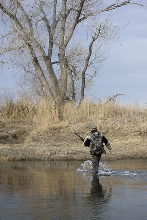 south platte river: Hunter (trapper) in camouflage cloths with a rifle and backpack crossing a shallow river (South Platte in Colorado) Stock Photo