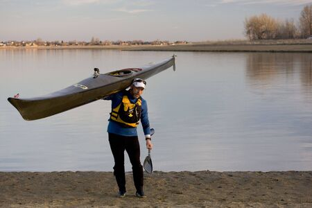 Maturemale paddler in a life jacket is carrying a long racing kayak and a wing paddle on a lake beach, early spring Stock Photo - 2619943