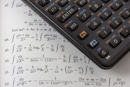 logarithm: Black programmable scientific calculator on a textbook open on integral tables.