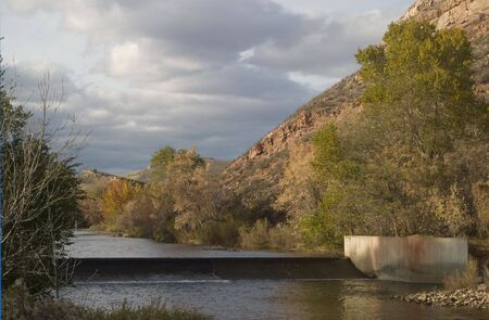 cache la poudre: A diversion dam for farmland irrigation on the Cache la Poudre River in foothills of Colorado Rocky Mountains above Fort Collins, late fall scenery with high cliffs and cloudy sky