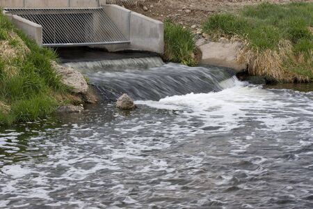 outflow: Processed and cleaned sewage flowing out from water reclamation facility to a river
