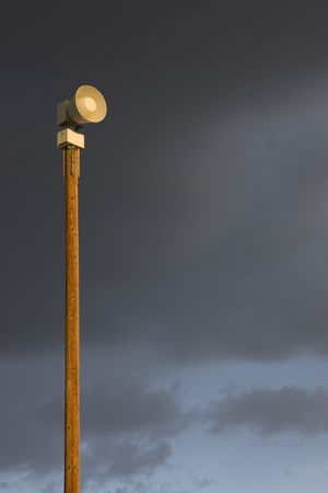 electromechanical: high decibel, battery operated,  electromechnical warning siren on a tall post against stormy sky