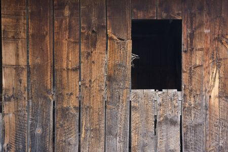 weathered and rough wood of old barn wall with saw cut pattern, a dark window opening