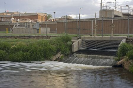outflow: Water reclamation plant with processed and cleaned sewage flowing out to the river Stock Photo