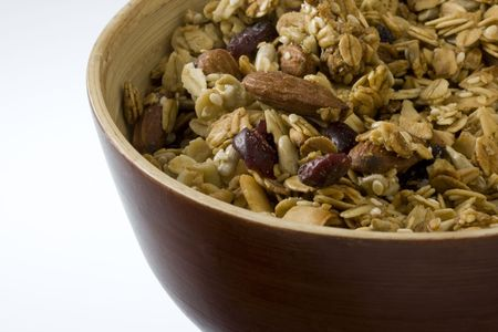 a wooden bowl of dry (no milk) natural granola with cranberries almonds, and other nuts; white copy space Stock Photo - 3169836
