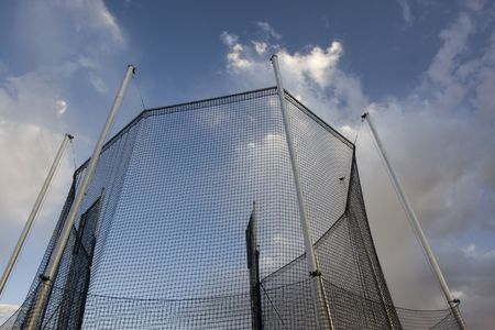 clody sky: protective cage for a hammer or ball throw competition against clody sky
