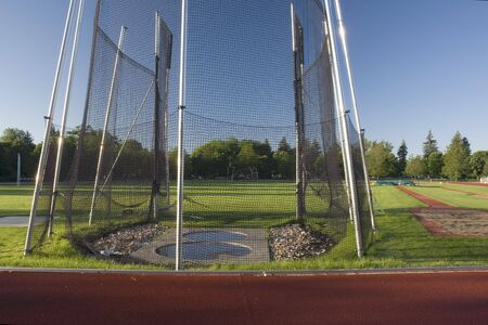 sand pit: green grass athletic field with a hammer throw cage and long jump sand pit, early morning light Stock Photo