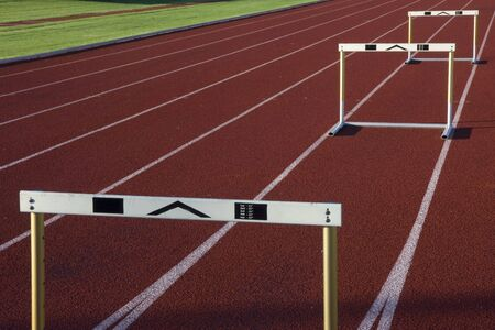 set up: red running tracks with three hurdles set up for training Stock Photo