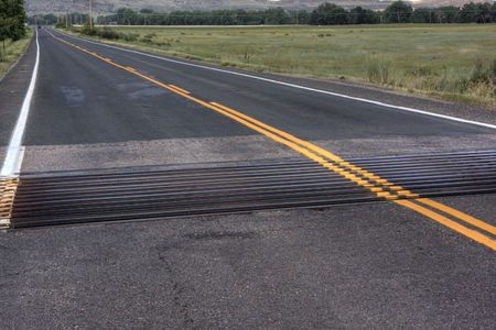 cattle guard: cattle guard across asphalt highway in Colorado with meadows and hills in background