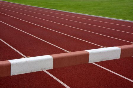 steeplechase: steeplechase barrier across red running tracks with white lines and green field in a background