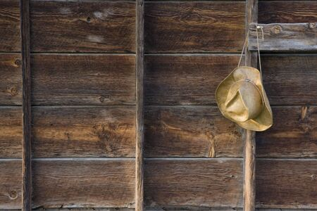 straw cowboy hat on the old barn wall  - weathered wood background Stock Photo - 3296522