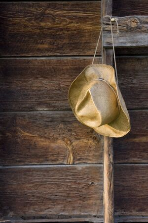 cowboy straw hat against weathered wood of old barn wall Stock Photo - 3331455