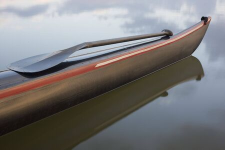 Carbon fiber gebogen schacht paddle op een slanke boeg van het racen dubbelschuin kano. Rustig meertje met wolk reflecties. Stockfoto